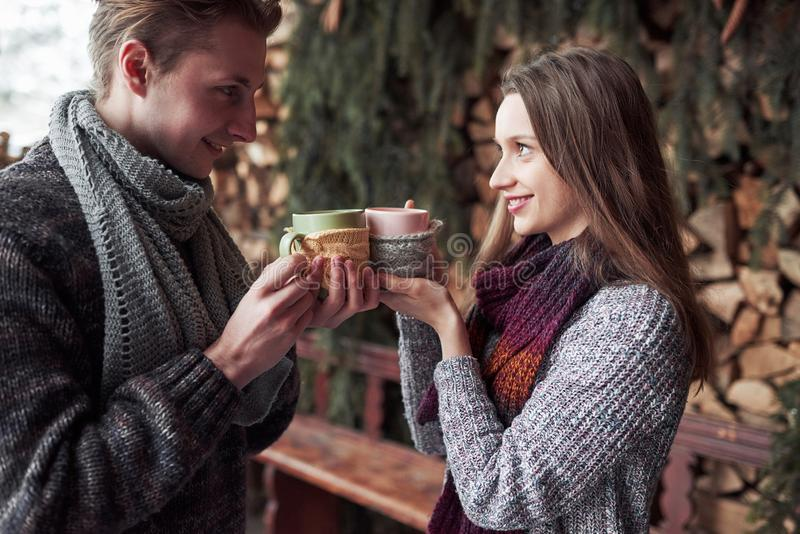 Young couple having breakfast in a romantic cabin outdoors in winter. Winter holiday and vacation. Christmas couple of royalty free stock photos