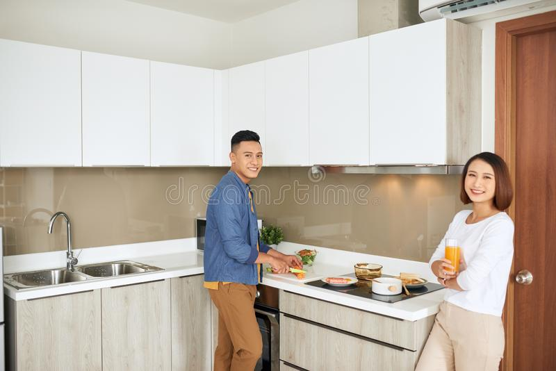 Young couple having breakfast, woman holding orange juice while man cooking food kitchen modern apartment interior royalty free stock photo