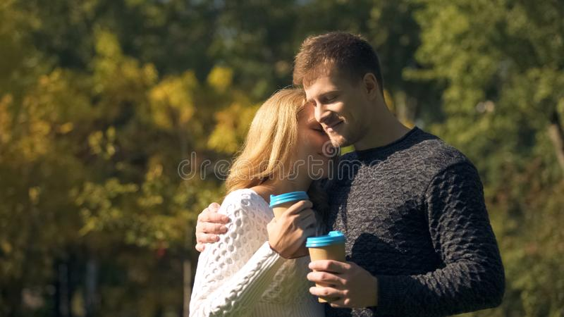 Young couple having coffee break in park, holding hot drinks and hugging, love royalty free stock photos