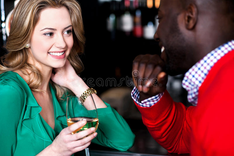 Young couple having conversation in bar. Young couple enjoying at bar, busy in romantic conversation royalty free stock image