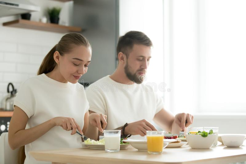 Young couple having dinner, tasting breakfast, eating together a royalty free stock photography