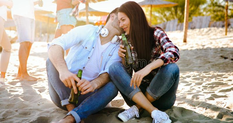 Young couple is having drinks on the beach stock photo