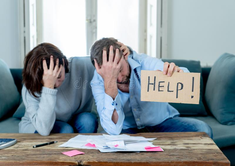 Young Couple having financial problems feeling stressed paying bills debts mortgage asking for help. Stressed young couple needing help in accounting home royalty free stock photo