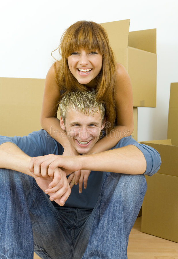Young couple having fun. Young couple sitting on the floor in flat. They're looking happy. Woman is hugging man. They're looking at camera. Front view royalty free stock image