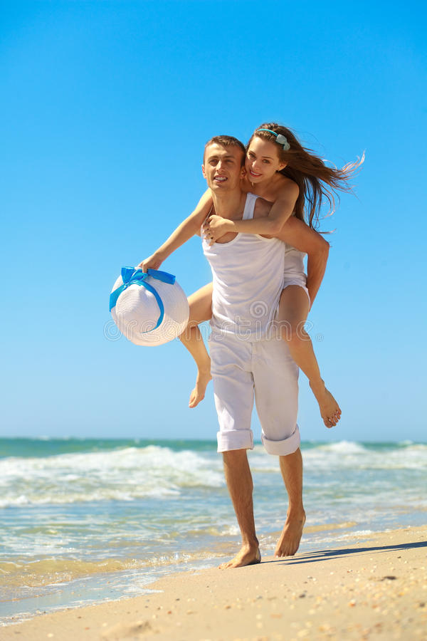 Young couple having fun on the beach. Portrait of a happy young couple having fun on the beach. Young men giving piggyback to women on beach.Couple enjoying a royalty free stock photos