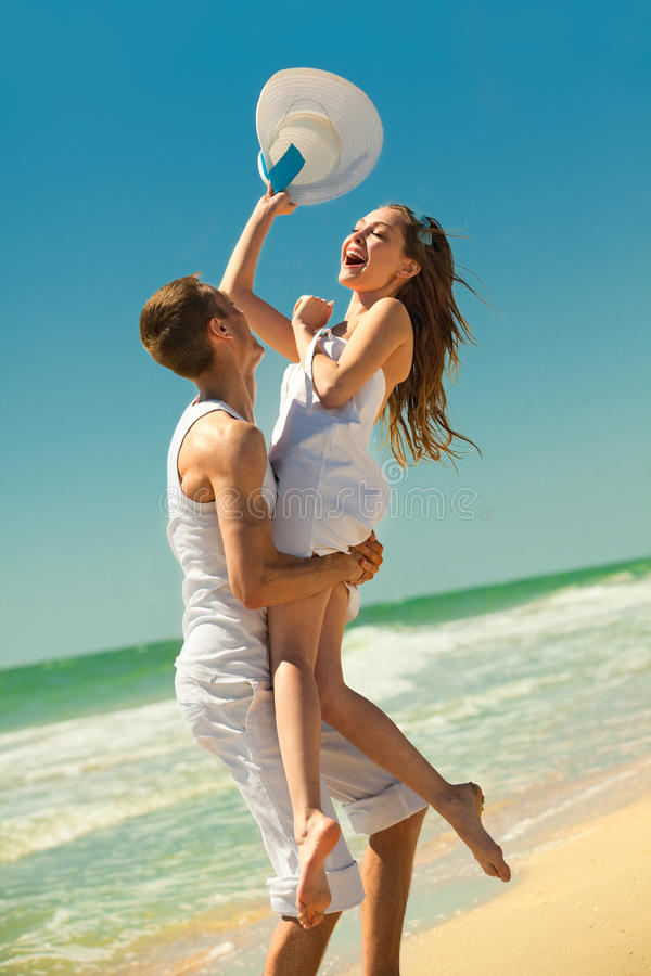 Young couple having fun on the beach. Portrait of a happy young couple having fun on the beach. Young men lifting his women on beach.Couple enjoying a summer royalty free stock photography
