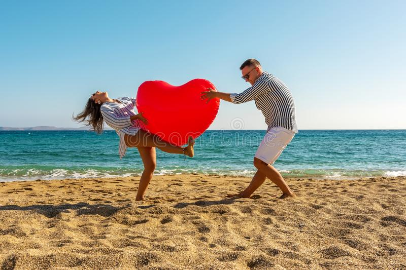 Young couple having fun on the beach with a big heart balloon. Summer love concept royalty free stock images