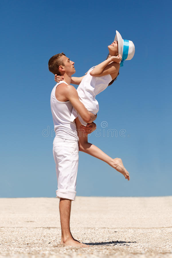 Young couple having fun on the beach. Portrait of a happy young couple having fun on the beach. Young men lifting his women on beach.Couple enjoying a summer royalty free stock image
