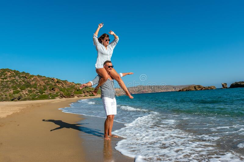 Young couple having fun on the beach. Summer vacations concept royalty free stock photography