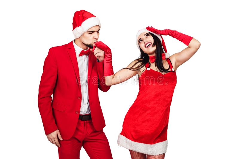 Young couple having fun at a christmas theme party. young man and woman in red suits with Santa hats. Young couple having fun at a christmas theme party. young royalty free stock images