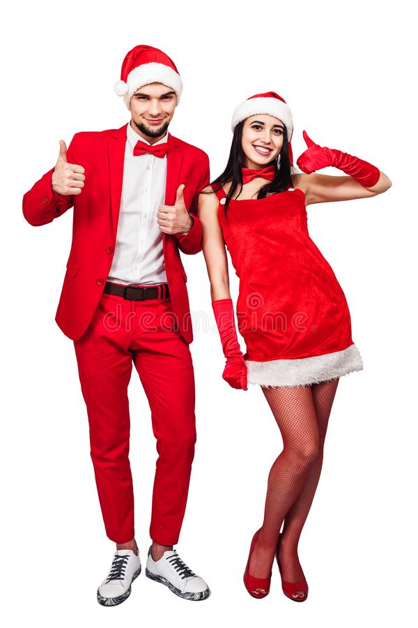 Young couple having fun at a christmas theme party. young man and woman in red suits with Santa hats. Young couple having fun at a christmas theme party. young royalty free stock photo