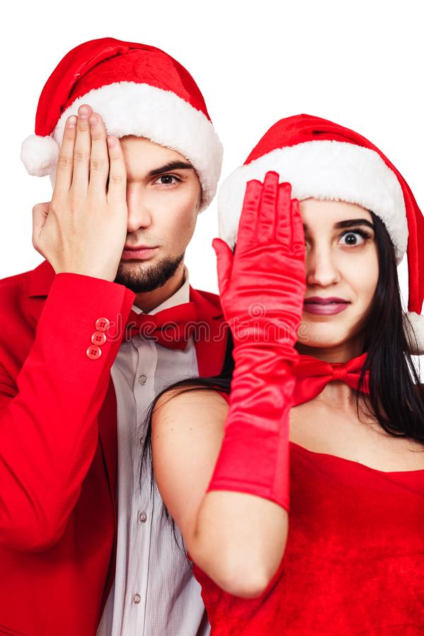 Young couple having fun at a christmas theme party. young man and woman in red suits with Santa hats. Young couple having fun at a christmas theme party. young stock photo