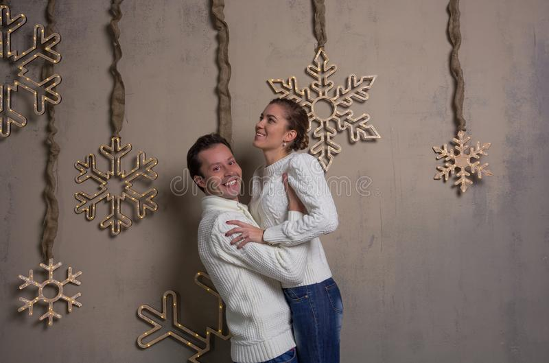 A young couple is having fun decorating a house for the new year. A young men lifted a girl in his arms near a wall with Christmas decorations. A young couple is stock photos