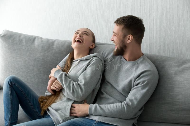 Young couple having fun laughing relaxing at home on couch. Young happy couple having fun talking laughing relaxing at home on couch, boyfriend embracing royalty free stock photo