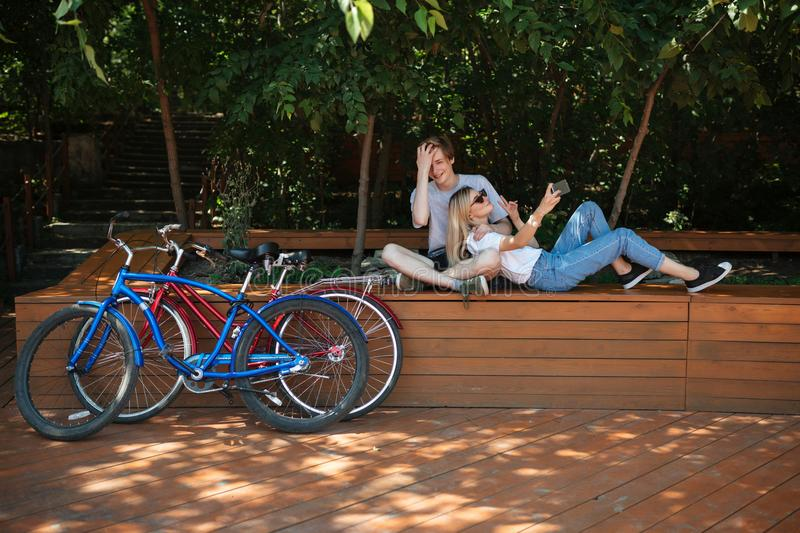 Young couple having fun in park with red and blue bicycles nearby. Cool boy sitting on bench in park with beautiful girl stock photo
