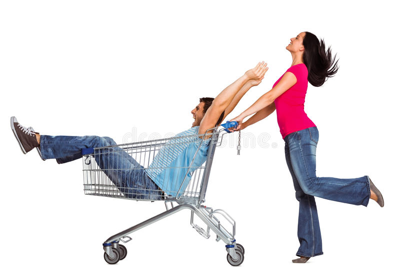 Young couple having fun with shopping cart stock image