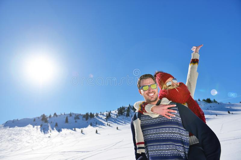 Young couple having fun on snow. Happy man at the mountain giving piggyback ride to his smiling girlfriend. Young couple having fun on snow. Happy men at the stock image