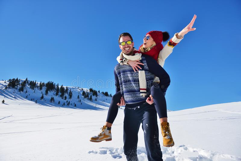 Young couple having fun on snow. Happy man at the mountain giving piggyback ride to his smiling girlfriend. Young couple having fun on snow. Happy men at the stock photography