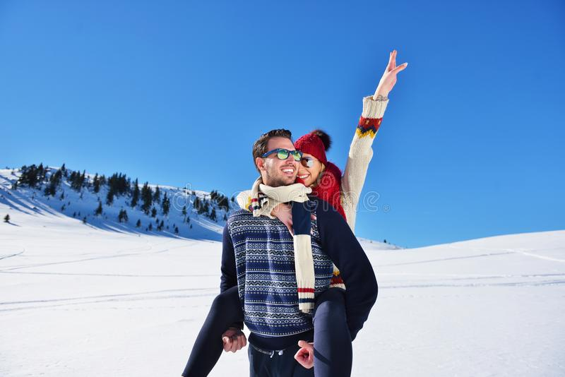 Young couple having fun on snow. Happy man at the mountain giving piggyback ride to his smiling girlfriend. Young couple having fun on snow. Happy men at the royalty free stock images