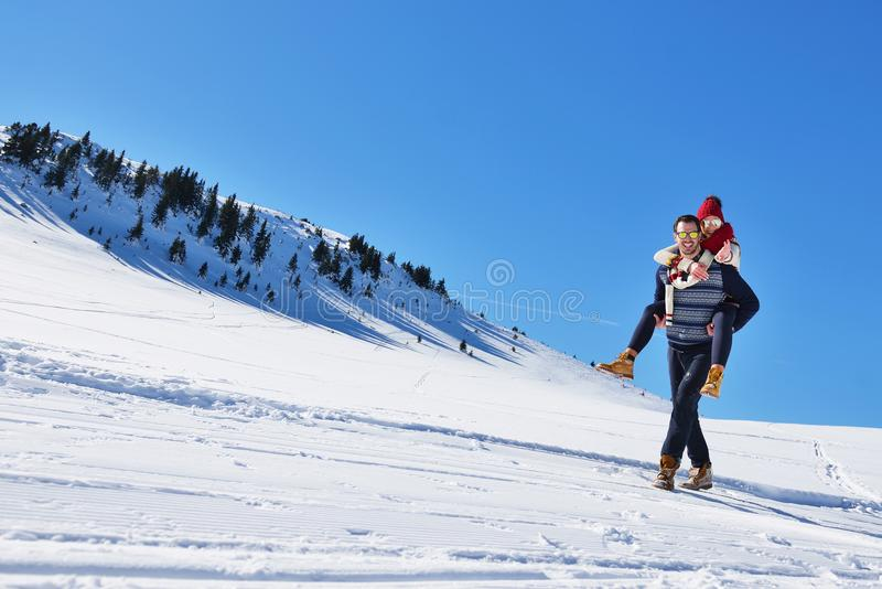 Young couple having fun on snow. Happy man at the mountain giving piggyback ride to his smiling girlfriend. Young couple having fun on snow. Happy men at the stock photo
