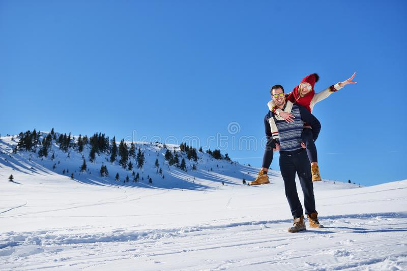 Young couple having fun on snow. Happy man at the mountain giving piggyback ride to his smiling girlfriend. Young couple having fun on snow. Happy men at the stock images