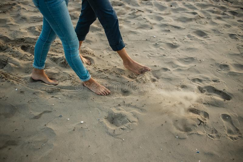 A young couple is having fun and walking on the sea coastline. Legs close up. Romantic date on the beach royalty free stock photo