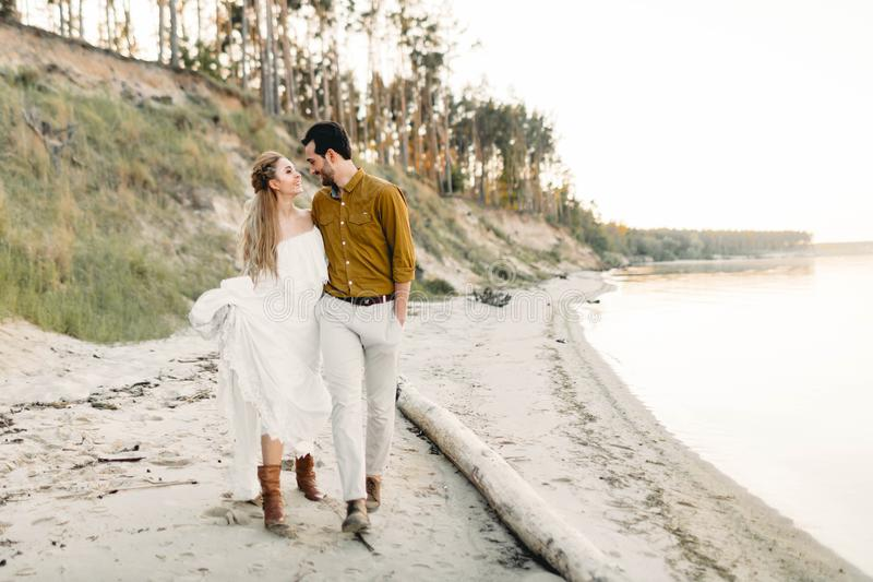 A young couple is having fun and walking on the sea coastline. Newlyweds looking at each other with tenderness. Romantic. Date on the beach. Wedding royalty free stock image