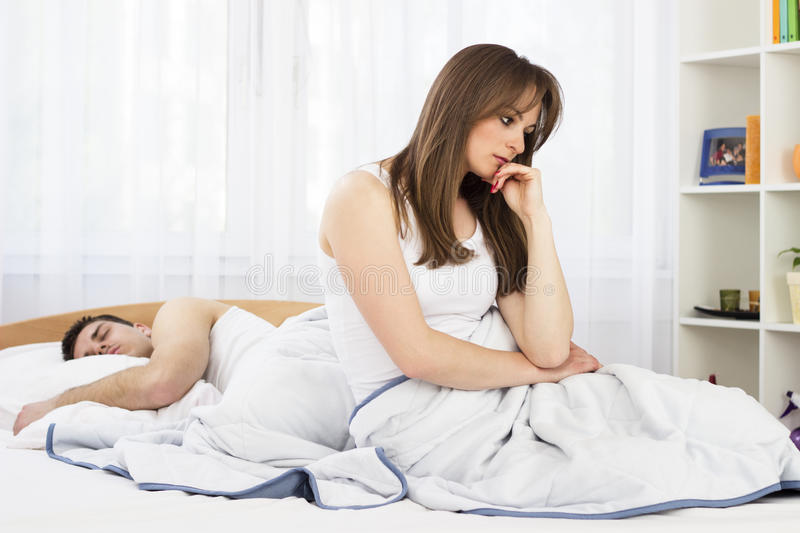 Young couple having relationship difficulties in t. Young female sitting looking depressed in bedroom stock photos