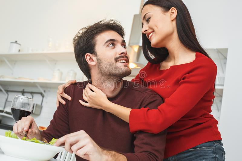 Young couple having romantic evening at home in the kitchen hugging close-up. Young men and women having romantic evening indoors in the kitchen having dinner royalty free stock photography