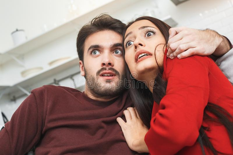 Young couple having romantic evening at home together watching horror scared. Young men and women having romantic evening indoors watching horror movie close-up royalty free stock images