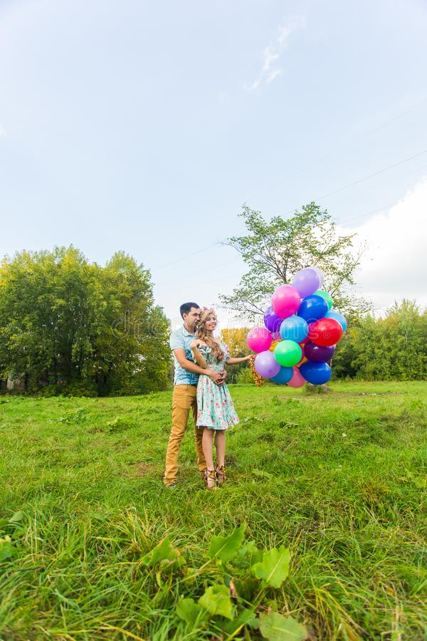 Young couple having weekend and walking with balloons on nature stock photography