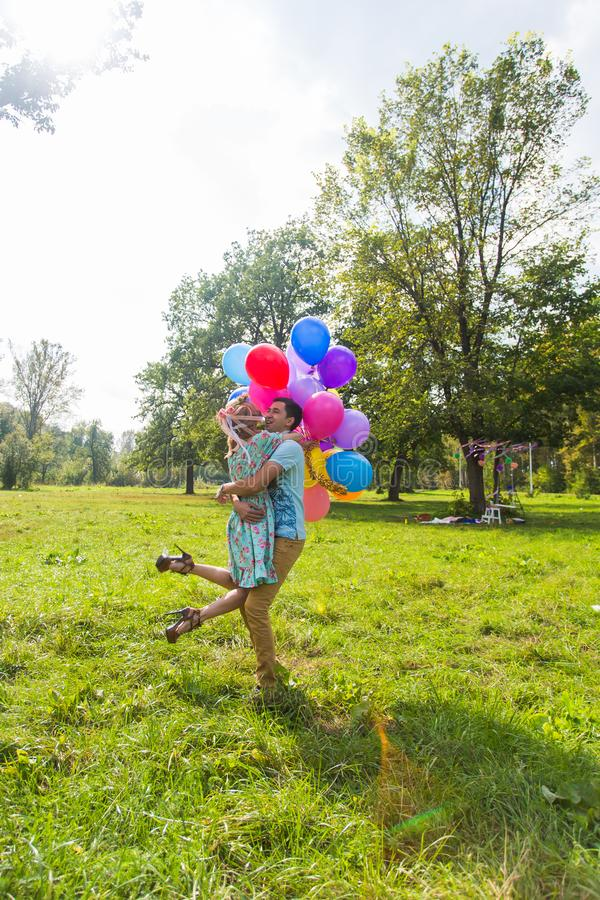 Young couple having weekend and walking with balloons on nature royalty free stock images