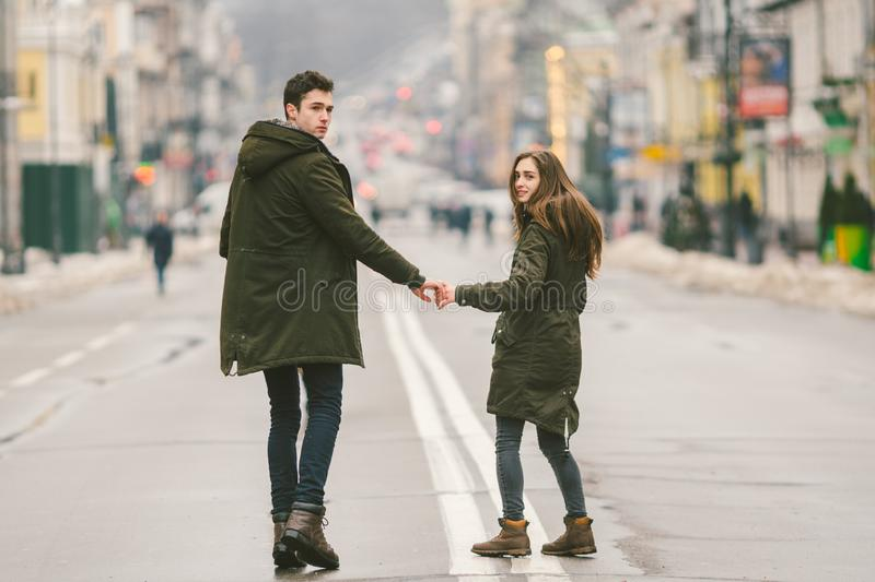 Young couple, heterosexual boy and girl of Caucasian nationality, loving couple, walk around the center of country of European. City in the middle of road on stock photo