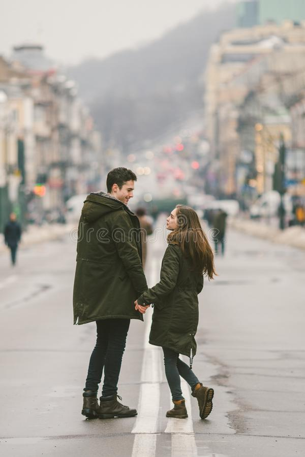 Young couple, heterosexual boy and girl of Caucasian nationality, loving couple, walk around the center of country of European. City in the middle of road on stock images