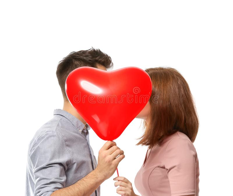Young couple hiding behind heart-shaped balloon on white background. Celebration of Saint Valentine's Day royalty free stock photo