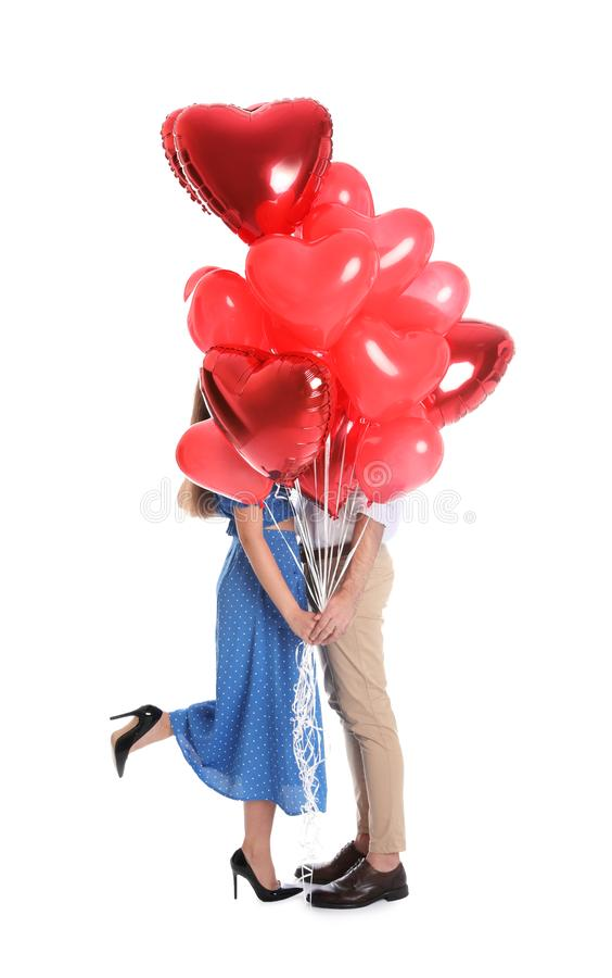 Young couple hiding behind heart shaped balloons isolated. Valentine`s day celebration stock image