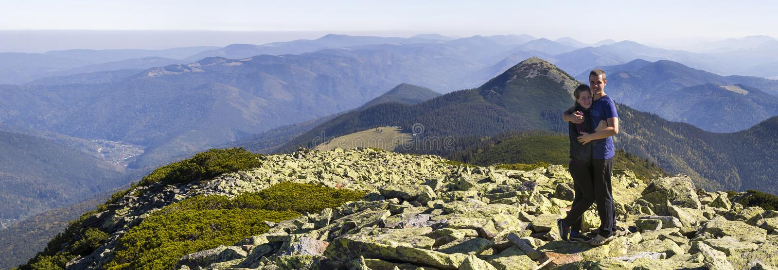 Young couple hike in Carpathian mountains. Man and woman standing on mountain top looking at beautiful landscape below. Wide panor. Ama of high rocky hills in royalty free stock image
