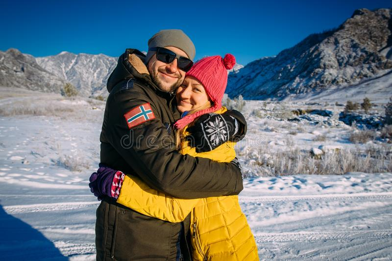 Young couple of hikers embracing and smiling against snowy hills during winter walk. Cheerful guy and girl in bright clothes hug stock photography