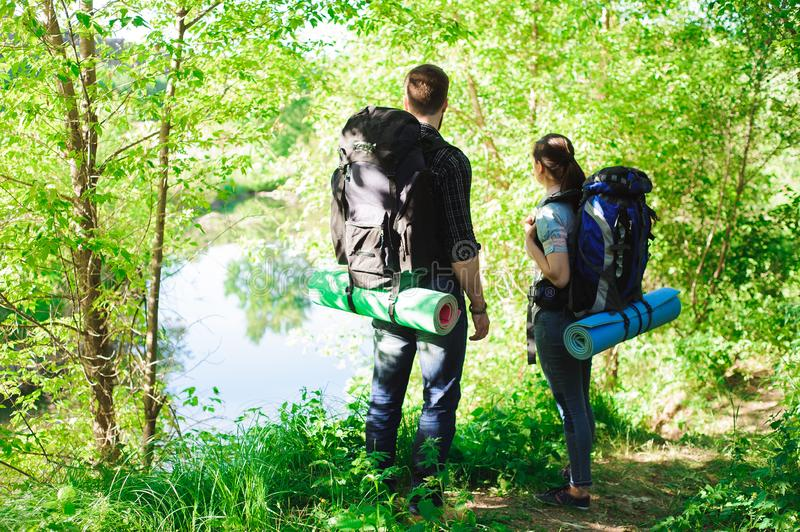 Young couple hikers in forest. sports man and woman with backpacks on road in nature. stock photo