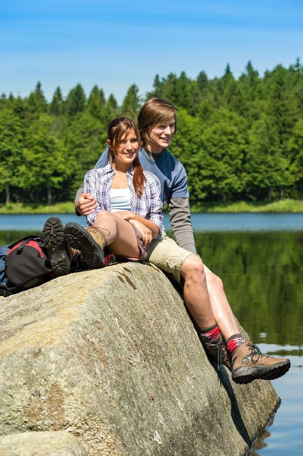 Young couple hikers lounging at lake nature. Young happy hikers couple lounging at lake beautiful nature royalty free stock photos