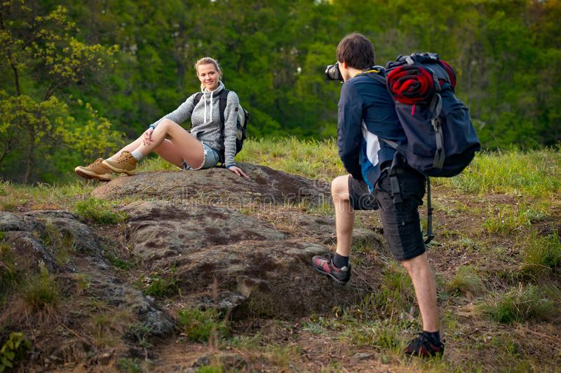 Young couple hikers resting. A man is taking photo of his girlfriend. Travel, vacation, holidays and adventure concept. Forest Mo stock photo