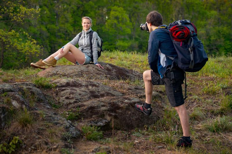 Young couple hikers resting. A man is taking photo of his girlfriend. Travel, vacation, holidays and adventure concept. Forest Mo stock photos