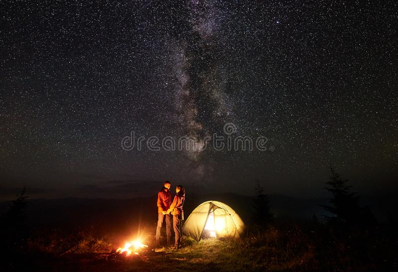 Young couple hikers resting near illuminated tent, camping in mountains at night under starry sky. Romantic couple tourists boy and girl standing near royalty free stock images