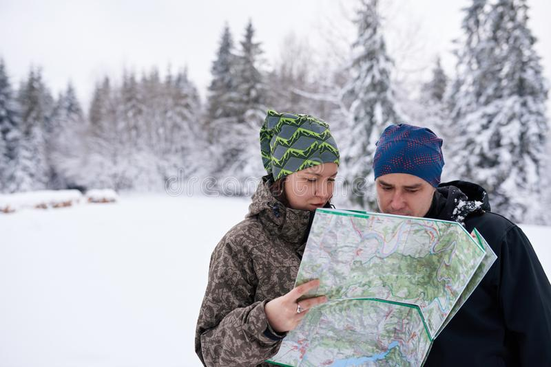 Young couple reading a map while hiking in winter royalty free stock photography