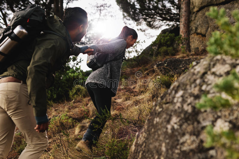 Young couple hiking in mountain. Female hiker helping her boyfriend uphill in the countryside. Young couple hiking in mountain royalty free stock images