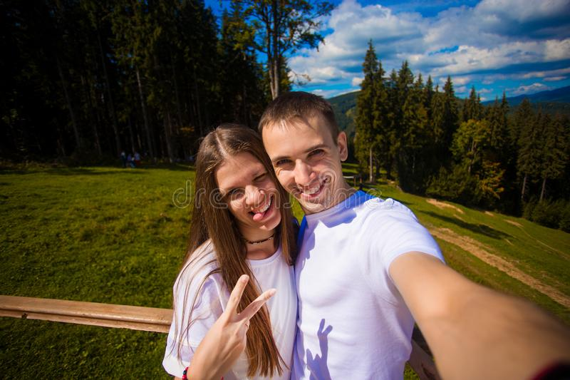 Young couple hiking taking selfie with smart phone. Happy young man and woman taking self portrait with mountain backgroun. Young couple hiking taking selfie stock photos