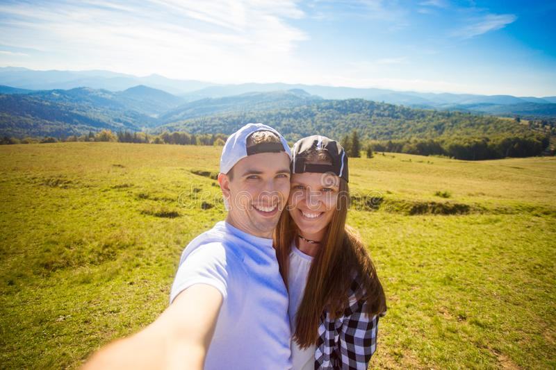 Young couple hiking taking selfie with smart phone. Happy young man and woman taking self portrait with mountain backgroun stock image