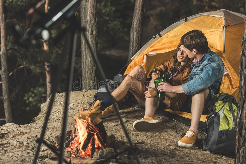 Young couple on hiking trip drinking beer. In tent royalty free stock photography