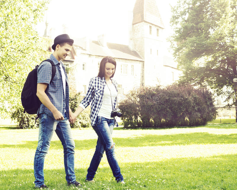 Young couple of hipsters: walking in park near castle. royalty free stock photos