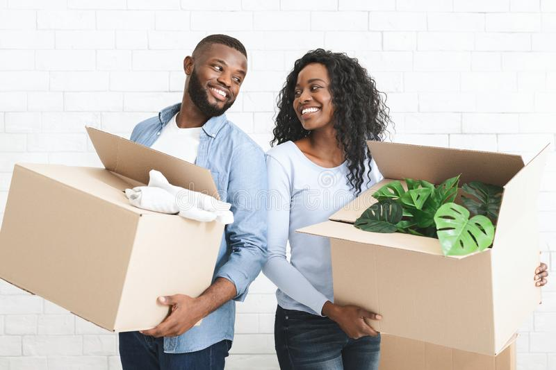 Young couple holding cardboard boxes, smiling to each other royalty free stock image